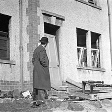 Bomb damage to 5 Oak Road, Parkhall in Clydebank after the Blitz in 1941. I.A. Howatson is inspecting the damage to his home. Gilbert Howatson gave me this photo, that is his father in the photograph. - Photograph supplied by Gilbert Howatson
