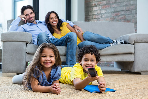 Smiling family in living room looking tv