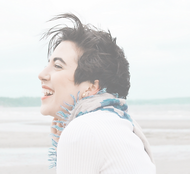 A white person with short tousled hair wearing a white sweater and blue scarf smiles on the beach