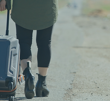 A person in an olive coat and black boots walks away towing a gray rolling suitcase behind them