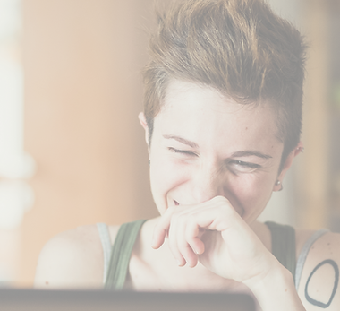 A white person in an olive top with a left shoulder geometric tattoo laughs at their computer