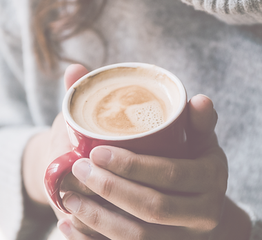 A person with curly brown hair wearing a gray slouchy turtleneck holds a latte in a red mug