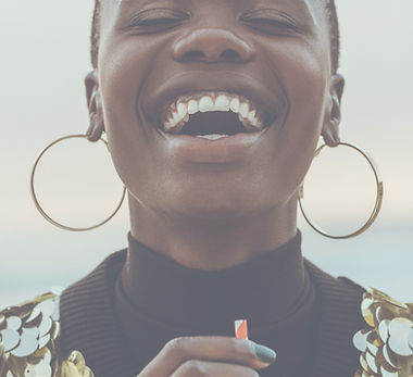 A Black person in a gold sequin top and hoop earrings laughs with their eyes closed holding a drink