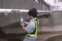 漏水調査の超音波流量測定を行なっている、株式会社 コスモリサーチの男性社員