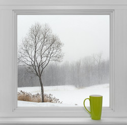 Green teacup on a windowsill, with winte