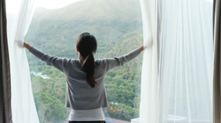 Woman open the window curtain at home