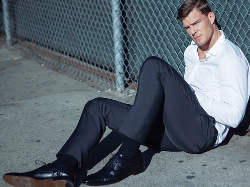 Alan Ritchson Leaning Against a Chain Link Fence