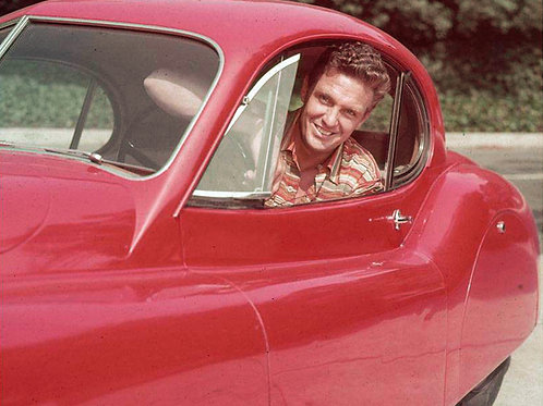 Robert Stack smiles while in the driver's seat of a Jaguar XK120 in 1955