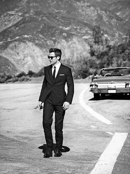 Chris Pine Wearing a Suit Walking Away From a Vintage Car