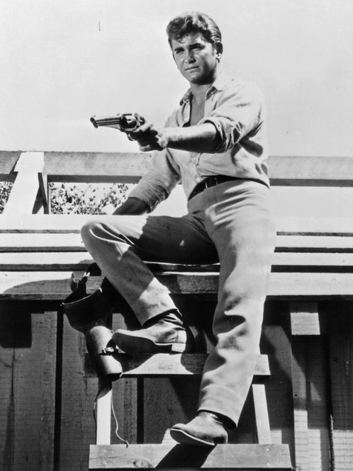 Michael Landon as Little Joe on a Ladder Aiming his Gun