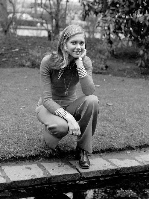 Young Olivia Newton-John Crouching on a Sidewalk