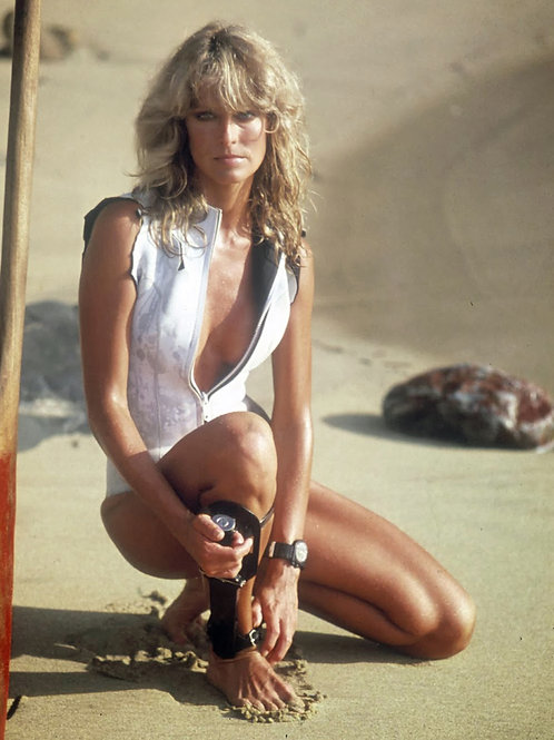 Beautiful Farrah Fawcett in a Sexy Swimsuit Crouching on the Beach