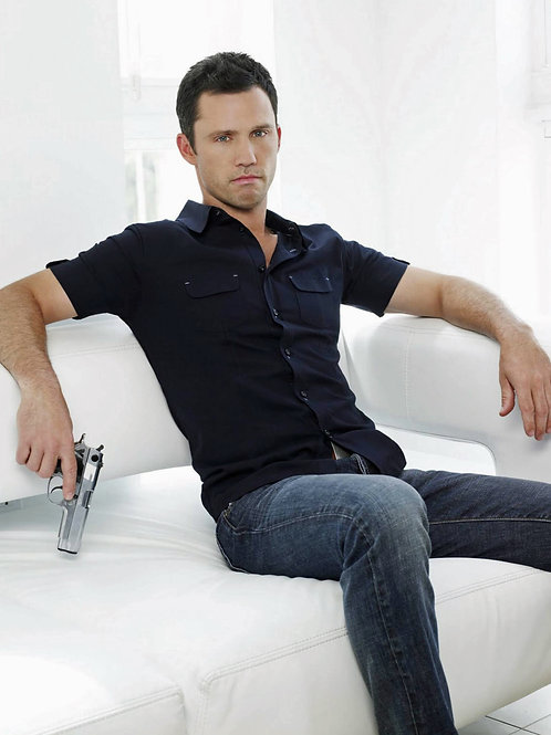 Jeffrey Donovan Sitting on a Sofa with a Pistol in his Hand
