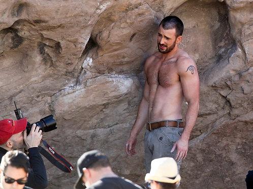 Shirtless Chris Evans Posing Near a Beach Boulder