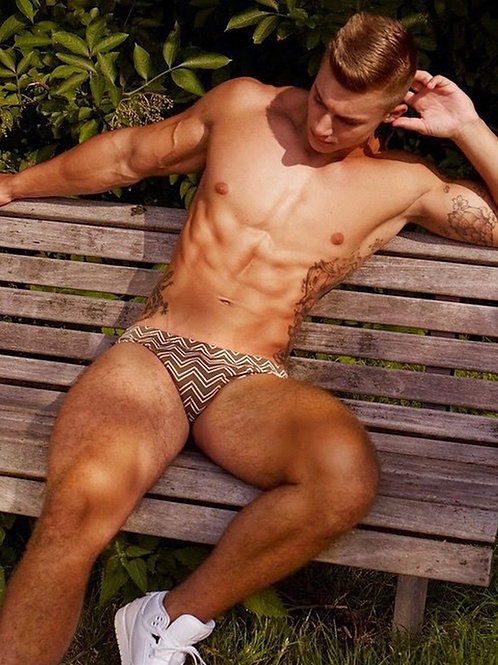 Muscular Guy in a Swimsuit Sitting on a Bench