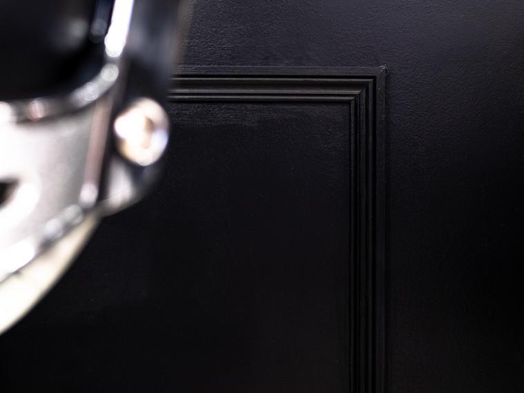 Architecture intérieure. Lyon. Architecte d'intérieur. Décorateur. Décoration d'un ancien institut de coiffure transformé en barber shop dans la ville de Villeurbanne à proximité de Lyon. Ambiance tout en noir et blanc pour donner du caractère et du style. Peinture avec des rayures. Crédence en carreaux de métro. Cimaise. Soubassement peint en noir. Mur noir. Suspension atelier. Fauteuil de barbier.   Atelier A.L
