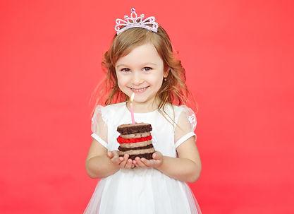 Little girl wearing crown holding a birt