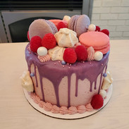 Garnished with macarons, meringues and fresh raspberries.