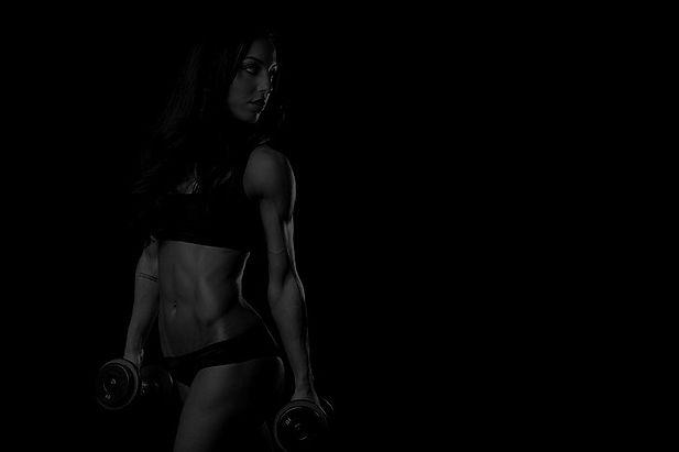 women-fitness-model-dumbbells-simple-bac