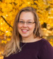 Headshot picture of counselor: female, mid 30s, long blonde-light brown hair, blue eyes with glasses, wearing matching earrings and necklace, wearing a maroon-colored sweater, outside in front of fall foliage