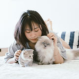 woman-lying-on-bed-with-two-cats-2215599