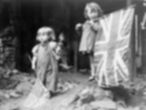 Two girls wave their flags in the rubble