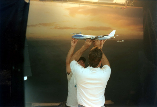 JJ Elam and Alan Faucher hanging Airforce One model in front of photo backing