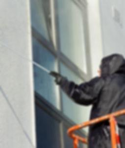 worker in cherry-picker washing a wall.j