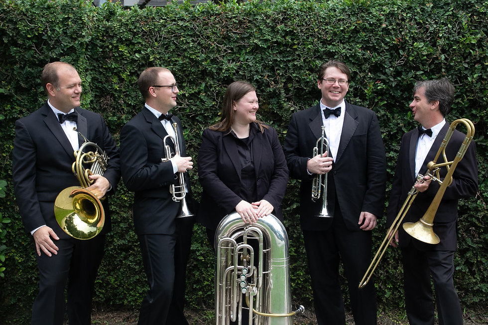 Brass Quintet laughs and smiles in front of green hedge outside church in Sanford, Florida