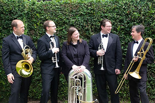 Brass Quintet standing in front of a green hedge, smiling and talking to each other, holding brass instruments