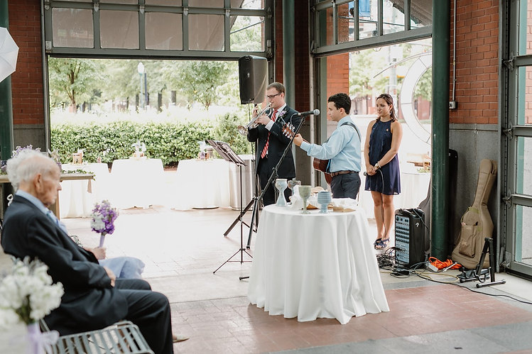 Trumpet and Guitar Musicians perform at wedding ceremony behind communion table