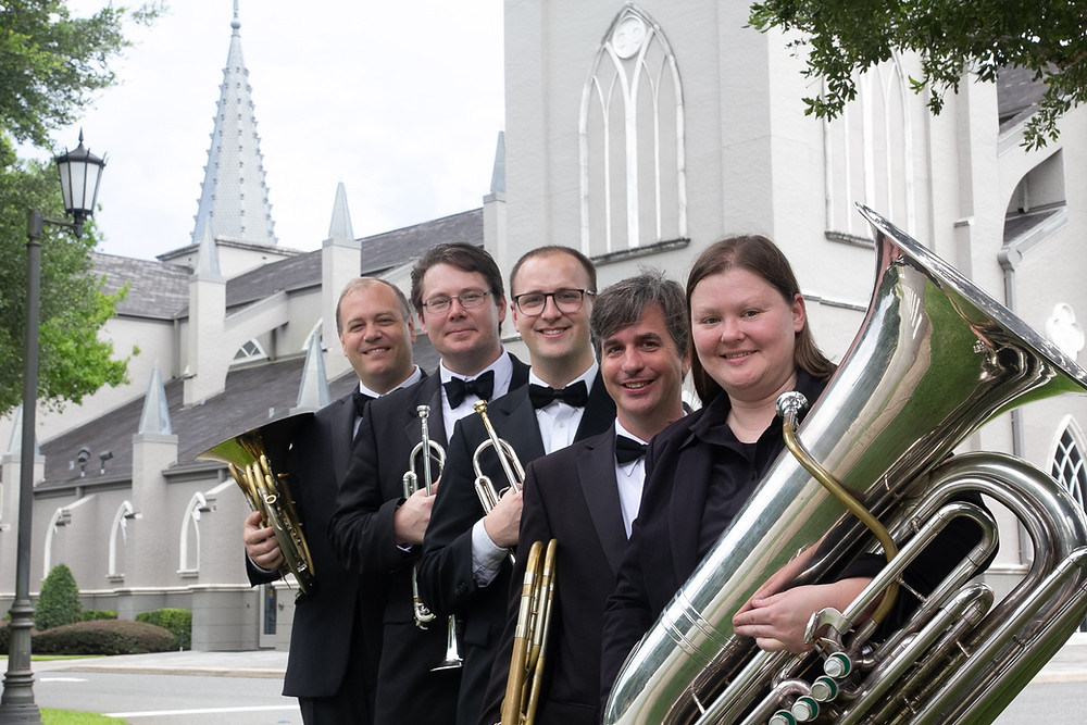 Brass Quintet of 2 Trumpets, Trombone, French horn, and tuba musicians stand in front of church steeple