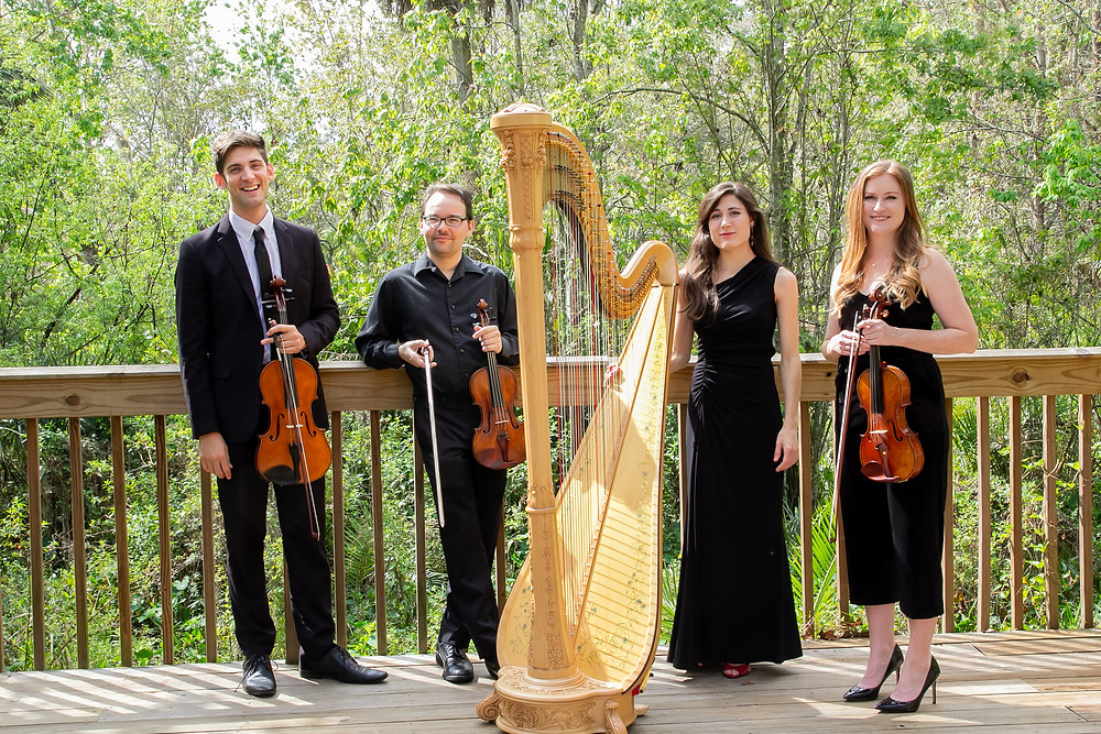 2 Violinist, a violist, and a harpist stand on boardwalk surrounded by trees