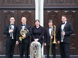Brass Quintet standing in front of traditional wooden church doors