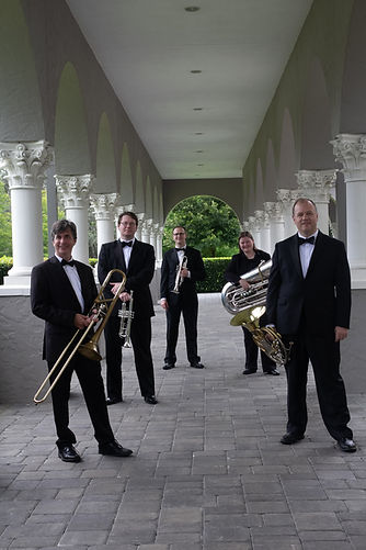 Brass Quintet stands in walkway. From front to back: Trmbone, French horn, trumpet, tuba, trumpet musicians stand in spread out formation