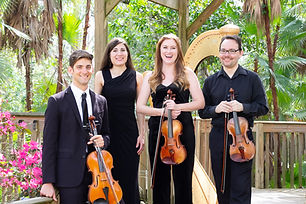 String and Harp Musicians Standing on a boardwalk in a park in Orlando holding violins and violas
