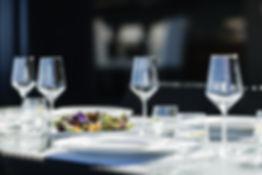 Kaunis ruoka-annos pöydällä viinilasien kanssa kesäpäivänä Helsingissä.