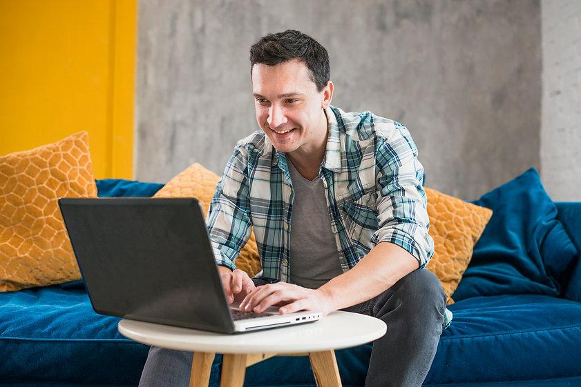 smiling-man-using-laptop-at-home.jpg