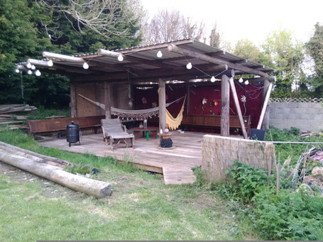 Garden shack made from reclaimed telegraph poles, scaffold boards and church pews