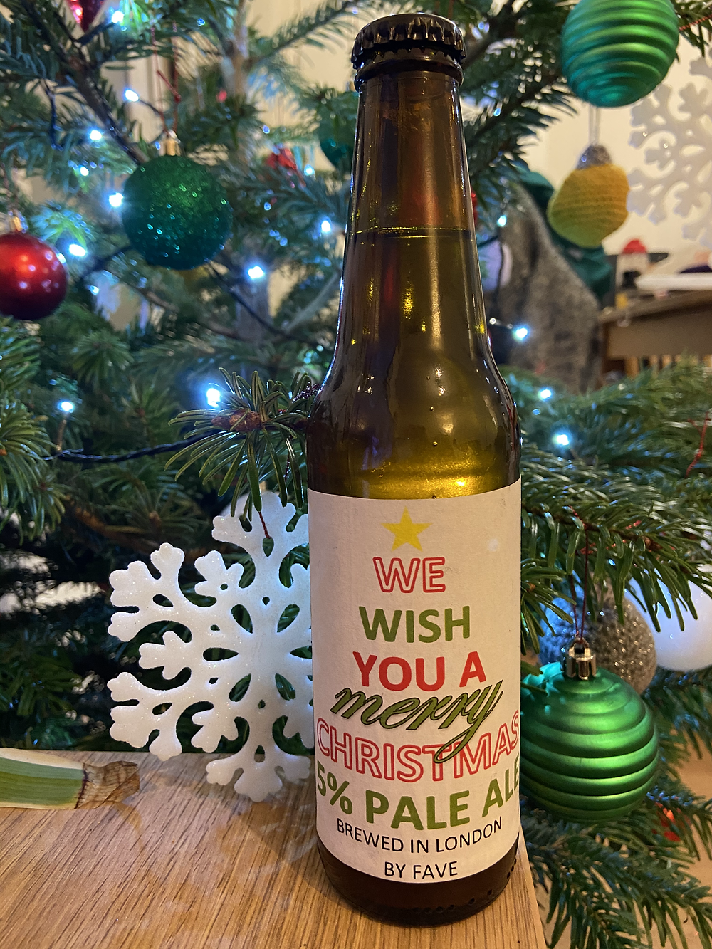 We wish you a Merry Christmas 5% pale ale bottle next to the Christmas tree