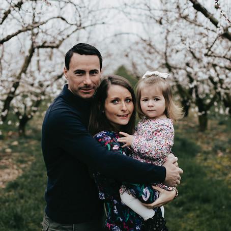 Une séance photo famille au milieu des arbres en fleurs.