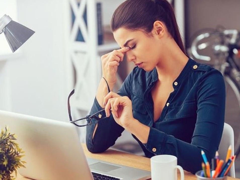 Mulher cansada  com os dedos no rosto e segurando os óculos. Estressada com esgotamento