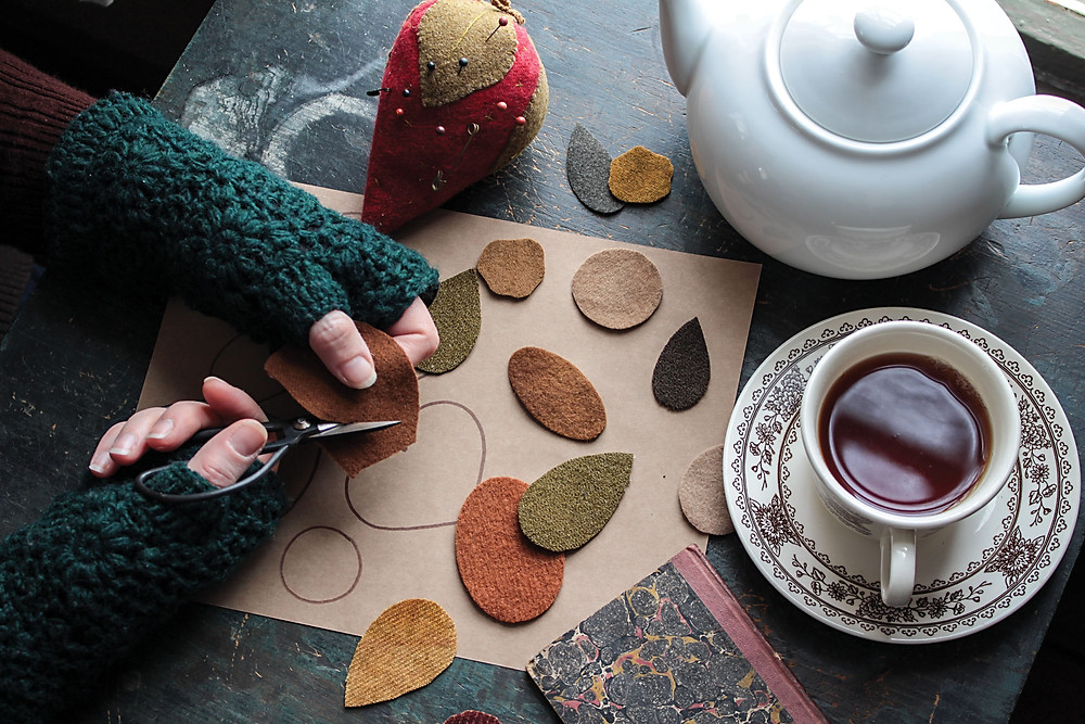woman with crocheted fingerless gloves cutting out wool pieces. A pot of tea and a teacup sit close by, along with a strawberry pincushion. Photo by Joseph P. Montion.