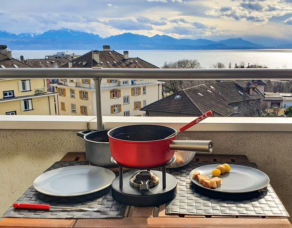 A table set for a Swiss cheese fondue for 2 in a balcony in front of the Geneva lake with a view to the Alps.