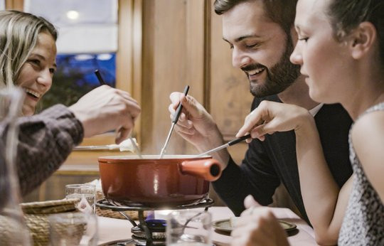 People having fun eating a Swiss cheese fondue.