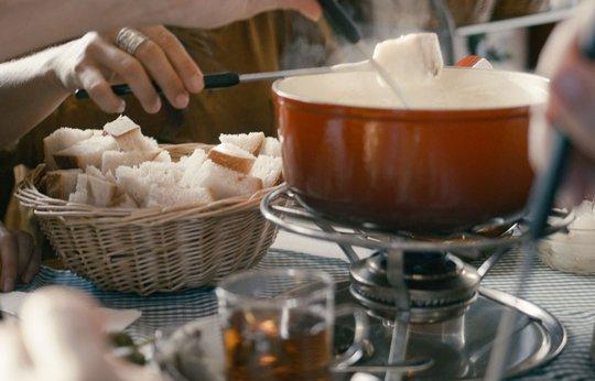 People eating Swiss cheese fondue, swiss fondue pot.