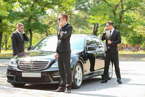 Handsome bodyguards near car outdoors.jp