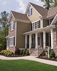 Suburban House in stone and wood with sidewalk and grass lawn