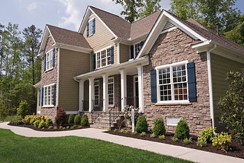 House with stone front, sidewalk, landscaping and green grass
