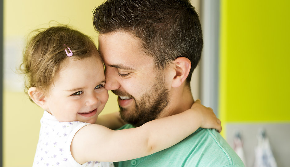 Indoor portrait of young father hugging